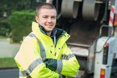 Jeune éboueur municipal près de camion à ordures images stock