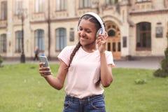 Jeune écolière à la position de cour d'école dans des écouteurs choisissant la chanson sur le smartphone gai image stock