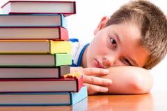 Jeune écolier déprimé observant ses manuels photo libre de droits