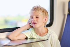 Jeune écolier dans le train avec le téléphone portable Image libre de droits