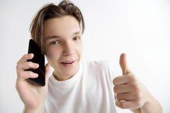 Jeune écran bel de smartphone d'apparence d'adolescent et OK de signature d'isolement sur le fond gris photographie stock libre de droits