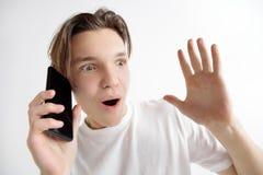 Jeune écran bel de smartphone d'apparence d'adolescent d'isolement sur le fond gris dans le choc avec un visage de surprise images stock