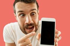 Jeune écran bel de smartphone d'apparence d'homme d'isolement sur le fond de corail dans le choc avec un visage de surprise photographie stock