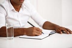 Jeune écriture africaine réussie d'homme d'affaires dans le carnet, séance sur le lieu de travail Photographie stock