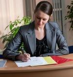 Jeune écriture attrayante de femme d'affaires Photographie stock libre de droits