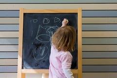 Jeune écriture caucasienne mignonne de garçon sur un tableau noir Photographie stock