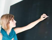 Jeune écriture d'étudiant sur le tableau noir Photo stock