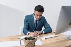 Jeune écriture d'homme d'affaires dans le carnet tout en travaillant à la table avec l'ordinateur de bureau photo stock