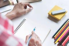 Jeune écriture de femme d'étudiant sur le carnet, effectuant le travail à la maison sur le bureau image stock
