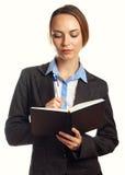 Jeune écriture de femme d'affaires dans son organisateur Photo stock