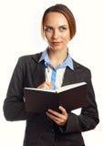 Jeune écriture de femme d'affaires dans son organisateur Photographie stock libre de droits