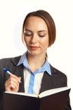 Jeune écriture de femme d'affaires dans son organisateur Photographie stock