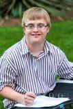 Jeune écriture handicapée d'étudiant dans le dossier dehors photos libres de droits