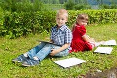 Jeune écriture heureuse de fille et de garçon Sourire dedans Image stock