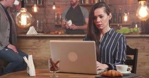 Jeune écrivain indépendant féminin composant un texte à son ordinateur portable banque de vidéos
