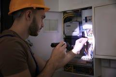 Jeune électricien avec la lampe-torche près de la boîte de commutateur photos stock