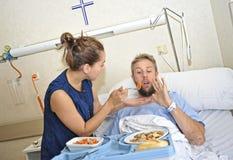 Jeune épouse essayant d'alimenter son mari réticent se situant dans le lit à la défectuosité de chambre d'hôpital après avoir été photographie stock libre de droits
