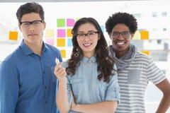 Jeune équipe créative souriant à l'appareil-photo Image stock