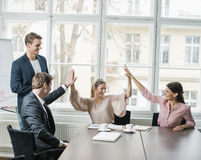 Jeune équipe d'affaires faisant la haute cinq à la table de conférence Photos stock