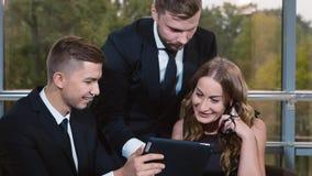 Jeune équipe d'affaires travaillant ensemble : observation des données sur le comprimé banque de vidéos