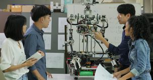 Jeune équipe d'ingénieur électronicien collaborant sur la construction du robot dans l'atelier banque de vidéos