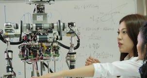 Jeune équipe d'ingénieur électronicien collaborant sur la construction du robot dans l'atelier clips vidéos
