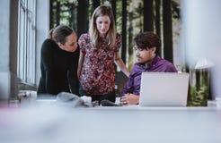 Jeune équipe de concepteurs discutant la publication de magazine Photographie stock libre de droits
