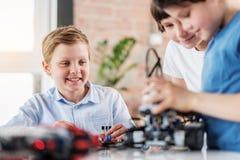 Jeune équipe gaie de techniciens utilisant le jouet Photographie stock
