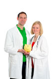Jeune équipe médicale amicale dans le manteau de laboratoire avec la tirelire Image stock