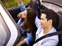 Jeune équitation asiatique de couples dans une voiture convertible Image libre de droits