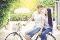 Jeune équitation asiatique de couples sur la bicyclette avec heureux et amusement au parc Image libre de droits