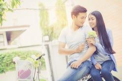 Jeune équitation asiatique de couples sur la bicyclette avec heureux et l'amusement Image libre de droits