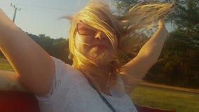 Jeune équitation blonde de femme dans une voiture convertible banque de vidéos