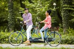 Jeune équitation de couples sur la bicyclette tandem Photo stock