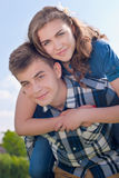 Jeune étreindre de couples d'équitation heureuse et ciel bleu Images stock