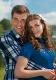 Jeune étreindre de sourire heureux de couples et ciel bleu Photographie stock