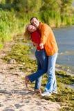 Jeune étreinte de couples d'amour sur la côte du fleuve Image stock