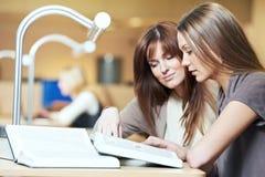 Jeune étude de fille d'étudiant avec des livres dans la bibliothèque Image libre de droits