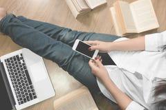 Jeune étudiant à l'aide du téléphone intelligent à la bibliothèque Image stock