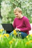 Jeune étudiant à l'extérieur avec l'ordinateur Photo libre de droits