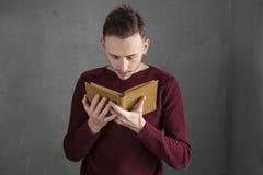 Jeune étudiant affichant un livre Photos stock