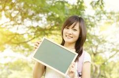 Jeune étudiant asiatique d'étudiante montrant le tableau vide Image stock