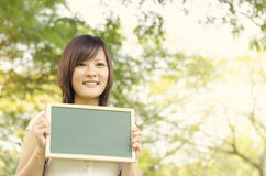 Jeune étudiant asiatique d'étudiante tenant le tableau vide Photographie stock