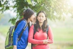 Jeune étudiant asiatique wishpering quelque chose à son ami Images stock