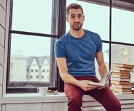 Jeune étudiant caucasien lisant un livre se reposant sur un filon-couche de fenêtre Image stock