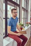 Jeune étudiant caucasien lisant un livre se reposant sur un filon-couche de fenêtre Photographie stock