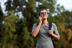 Jeune étudiant caucasien utilisant le téléphone portable dehors en parc public photographie stock libre de droits