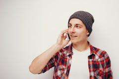 Jeune étudiant dans la chemise rouge occasionnelle parlant sur le smartphone Photos libres de droits