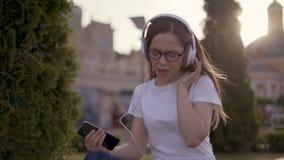 Jeune étudiant drôle s'asseyant sur l'herbe en parc et écoutant la musique dans de grands écouteurs fille chantant le long clips vidéos