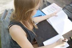 Jeune étudiant en dehors de la lecture et des notes de prise Photographie stock libre de droits